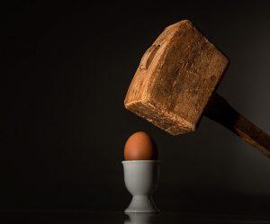 A hammer destroying an egg.