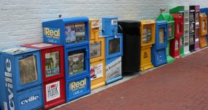 Over ten different newspaper boxes, side by side.