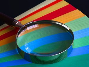 Magnifying glass on colorful surface.