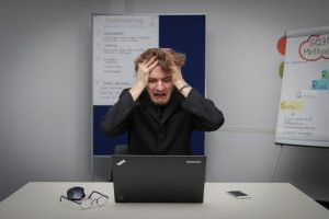 Frustrated man in front of computer.