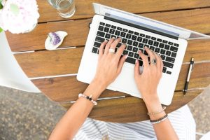 Woman exploring the benefits of guest blogging for growing businesses on her laptop.