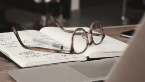 glasses and a notebook on a desk