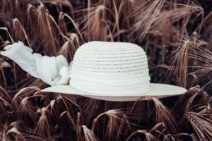 White hat on dried brown leaves.