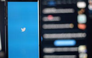 Twitter logo on phone screen.