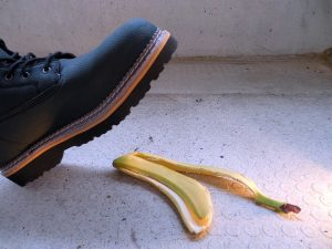 A boot almost stepping on the banana.