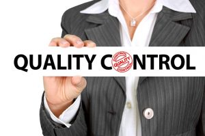 """A woman holding the """"quality control"""" warning."""