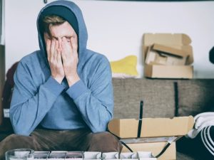 A nervous man sitting on a sofa.