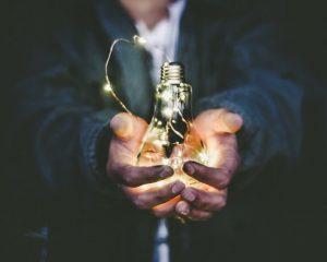 A lit up lightbulb in a mans hands