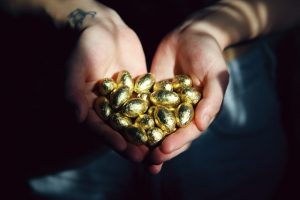 A person holding small gold eggs.