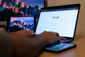 A man is typing something in a Google search. Google can take an important part in removing spammy backlinks from your website.