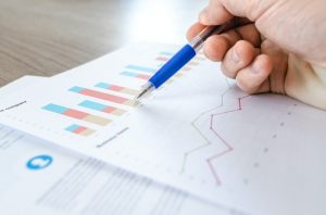 There is a person holding a pen, pointing to a paper with some graphs.