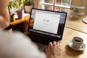 A person is typing something on Google. Browsing the information about the websites that have backlinks to your site is an important step to make before you start cleaning up your bad backlinks.