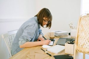 A woman is writing something down in her notebook. Collecting the information is the first step in the process of Original research- one of the types of content that attract the most backlinks.