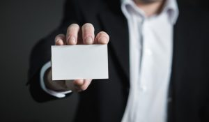 A man in a suit is holding a small blank piece of paper.