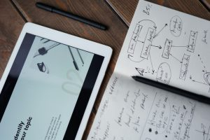 There is a pen, and a notebook with some notes and drawings in it.