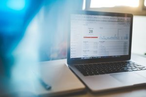 There is a laptop on the desk, showing some analytics on its screen. If you analyze your backlink profile regularly, you can keep track of all 3 types of backlinks on your site.